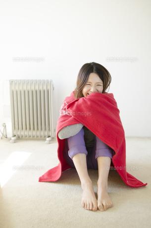 オイルヒーターの前で赤いストールに包まる女性の写真素材 [FYI01703815]