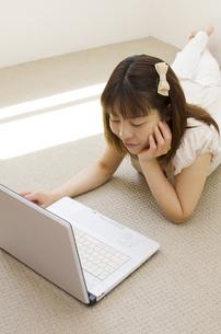 床に寝そべりノートパソコンをいじる女性の写真素材 [FYI01703819]