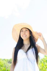 白いワンピースに帽子をかぶって笑うロングヘアの女性の写真素材 [FYI01703841]