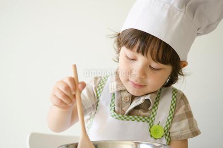 コック帽子を被って料理をするハーフの男の子の写真素材 [FYI01703952]
