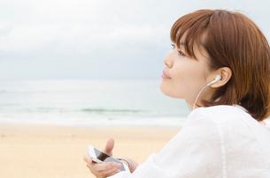 ビーチに座りスマートフォンで音楽を聴く女性の写真素材 [FYI01703958]