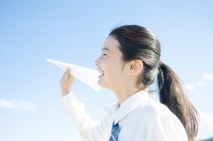 紙飛行機を持つ制服姿の女の子の写真素材 [FYI01703963]