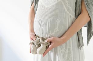 ベビーシューズと妊婦のお腹の写真素材 [FYI01703988]