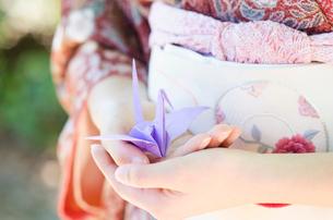 着物姿の女性の手の上に乗せた折り鶴の写真素材 [FYI01704028]