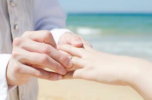 海をバックに指輪交換をしている手のアップの写真素材 [FYI01704076]