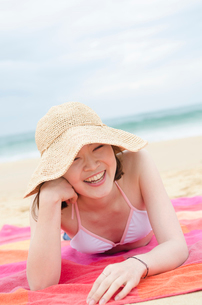 帽子をかぶってビーチに寝そべって笑うビキニ姿の女性の写真素材 [FYI01704099]