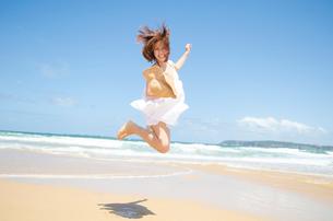 ビーチでジャンプをする女性の写真素材 [FYI01704109]