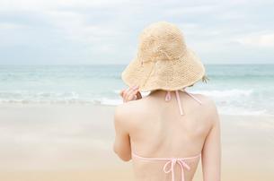 帽子をかぶってビーチにたたずむビキニ姿の女性の後姿の写真素材 [FYI01704112]