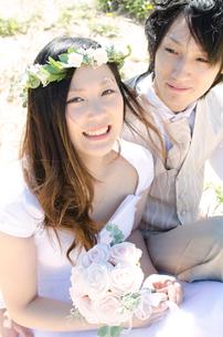 花冠を付けブーケを持って笑顔の女性と見つめる男性の写真素材 [FYI01704121]