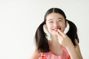 イチゴを持って笑うハーフの少女の写真素材 [FYI01704132]