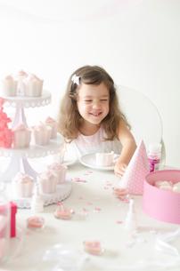 ピンクテーマのパーティで笑顔のハーフの女の子の写真素材 [FYI01704155]