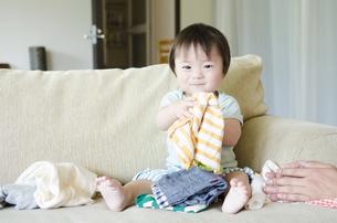 室内でソファに座って洋服を持つ男の子の写真素材 [FYI01704156]