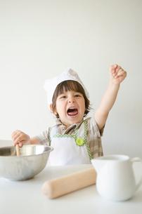 コック帽子を被って手を挙げるハーフの男の子の写真素材 [FYI01704217]