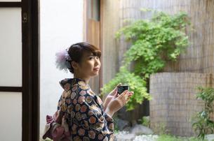 縁側に座ってお茶の入った湯のみを持つ着物姿の女性の写真素材 [FYI01704233]