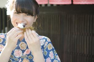 柏餅を食べながら笑う着物姿の女性の写真素材 [FYI01704238]