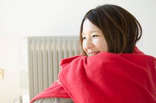 オイルヒーターの前で赤いストールに包まる女性の写真素材 [FYI01704259]