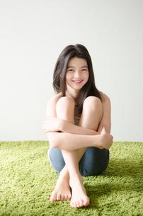 グリーンのラグの上に座ったハーフの少女の写真素材 [FYI01704273]