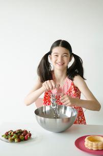 クリームを泡立てる笑顔のハーフの少女の写真素材 [FYI01704288]