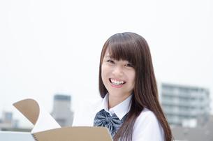 ノートを持って笑う制服姿の女性の写真素材 [FYI01704314]