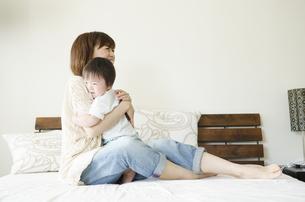 ベッドの上で抱き合うお母さんと男の子の写真素材 [FYI01704324]