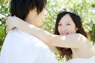 男性の肩に手を回してこちらを見る花冠を付けた女性の写真素材 [FYI01704326]