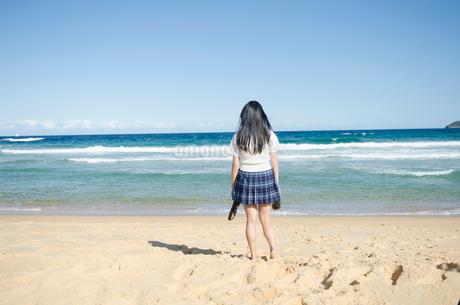 両手に靴を持ってビーチにたたずむ制服姿の女の子の写真素材 [FYI01704328]