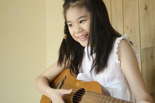 ギターを弾いている女の子の写真素材 [FYI01704334]