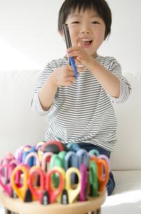 たくさんのはさみで遊ぶ男の子の写真素材 [FYI01704392]