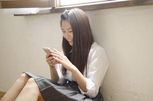 床に座って携帯電話を見ている制服姿の女性の写真素材 [FYI01704393]