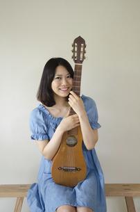 ギターを抱えている笑顔の女性の写真素材 [FYI01704400]