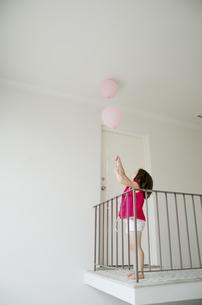 白い空間でピンクの風船を持つの女の子の写真素材 [FYI01704404]