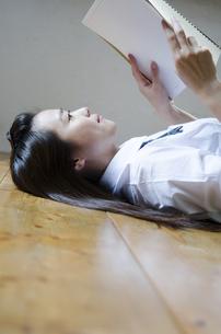 床に寝転がってノートを眺める制服姿の女性の写真素材 [FYI01704409]