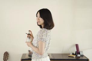 部屋の中でスプレーを手にしている女性の写真素材 [FYI01704417]
