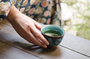 お茶の入った湯のみと女性の手の写真素材 [FYI01704422]
