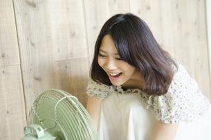 扇風機に向かって声を出している女性の写真素材 [FYI01704439]