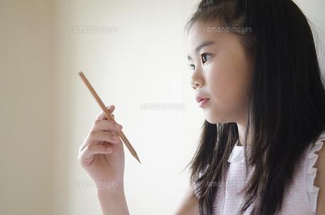 鉛筆を持って考えている女の子の写真素材 [FYI01704449]