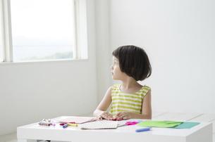 折り紙で遊びながら外を眺める女の子の写真素材 [FYI01704508]