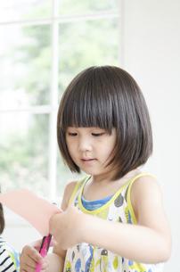 紙を切っている女の子の写真素材 [FYI01704579]