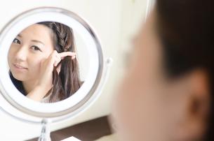鏡を見ながら髪をいじる女性の写真素材 [FYI01704608]