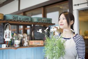 お花の鉢を持っている女性の写真素材 [FYI01704636]