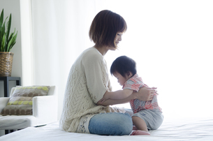 ベッドの上に座っている男の子とお母さんの写真素材 [FYI01704640]