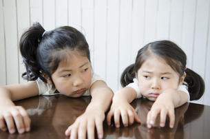 机に腕を乗せてにらみ合う姉妹の写真素材 [FYI01704659]