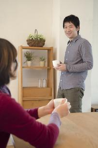 カップを持った女性越しに笑顔の男性の写真素材 [FYI01704668]