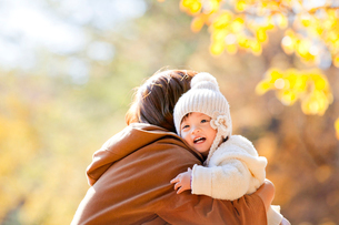 紅葉の公園で遊ぶ母と娘の写真素材 [FYI01704671]