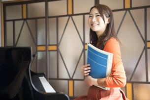 ピアノの前で楽譜を持っている女性の写真素材 [FYI01704674]