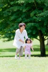 公園で娘を追いかける母親の写真素材 [FYI01704678]