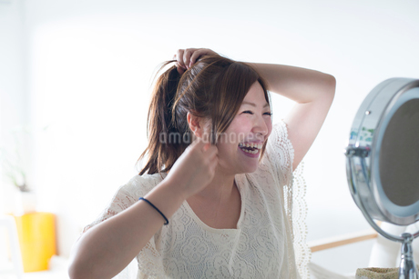 鏡を見ながら髪を結ぶ女性の写真素材 [FYI01704710]