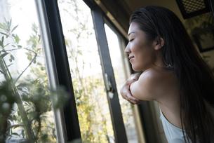 窓辺でストレッチをしている女性の写真素材 [FYI01704739]