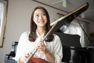 ピアノの前でフルートを持っている女性の写真素材 [FYI01704760]