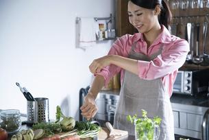 キッチンで腕まくりをしている女性の写真素材 [FYI01704761]
